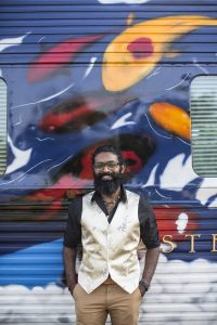 Indian man next to painted train exterior