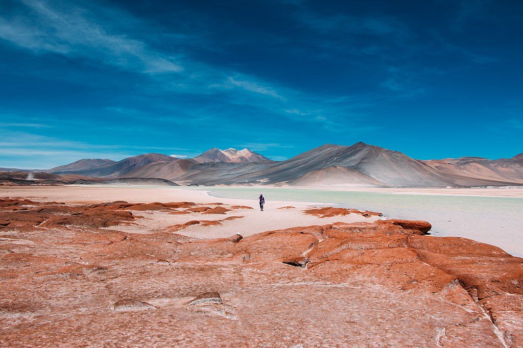 orange desert earth with clear blue skies and man in distance