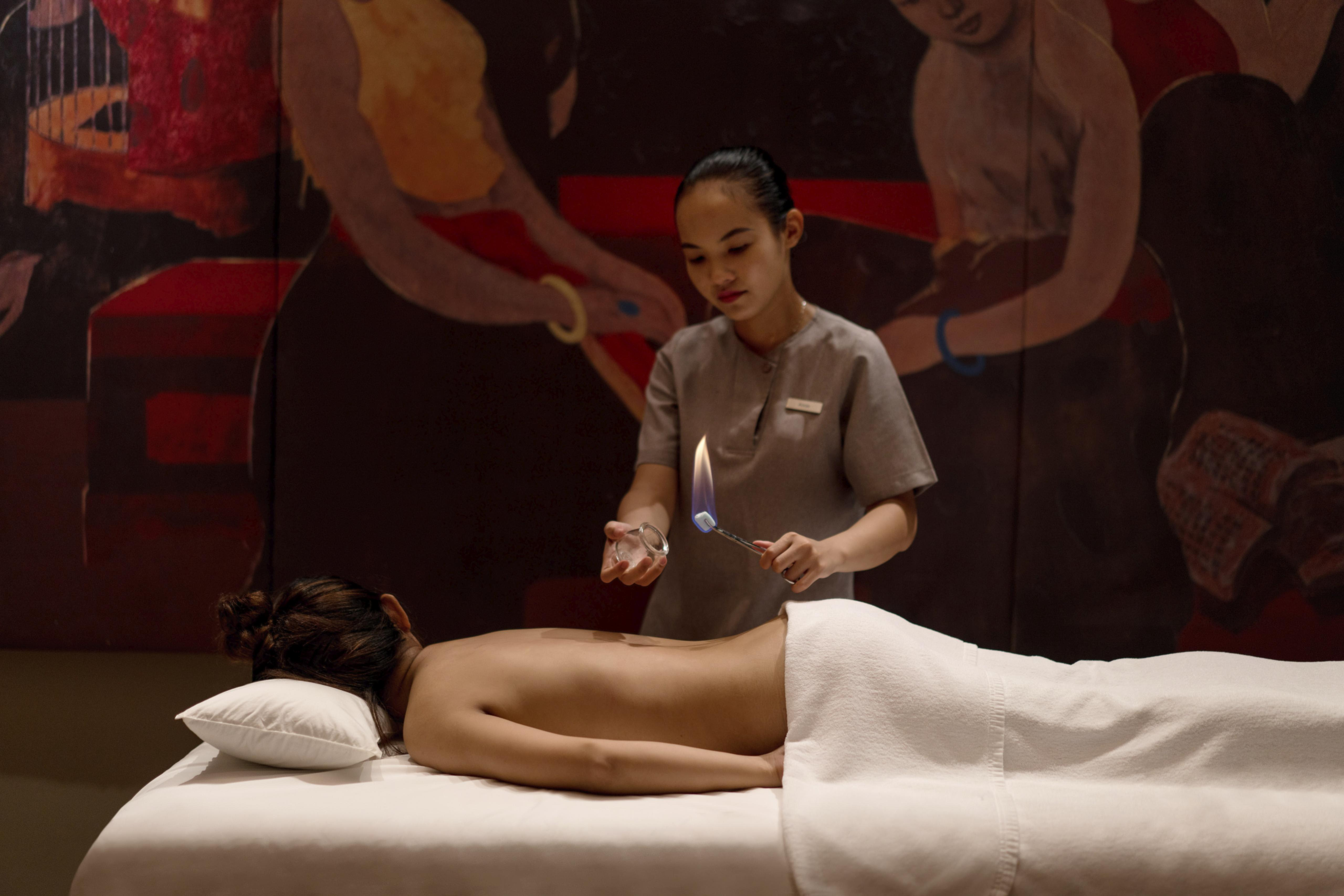 woman face down on massage table, masseuse