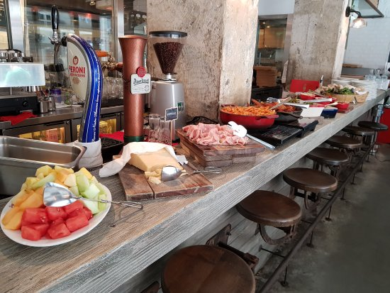 counter with plates of fruit, cheeses, salads and meats