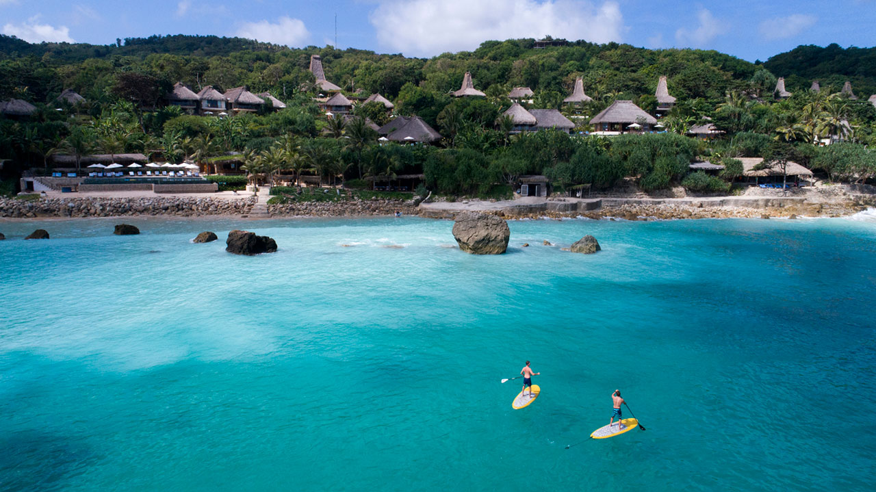 two paddle boarders on clear blue water