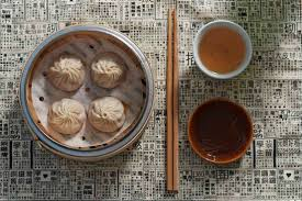 four buns on plate, chopsticks and dipping sauce
