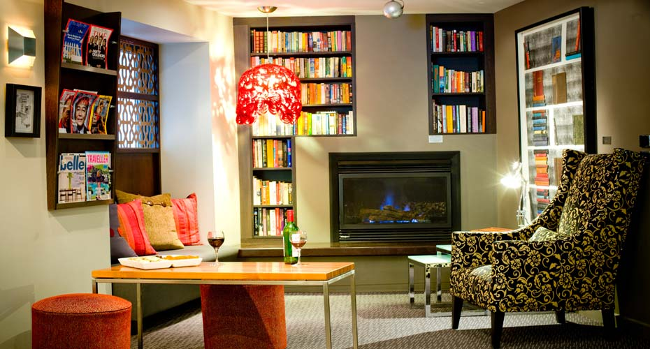 hotel sitting area with fireplace and books