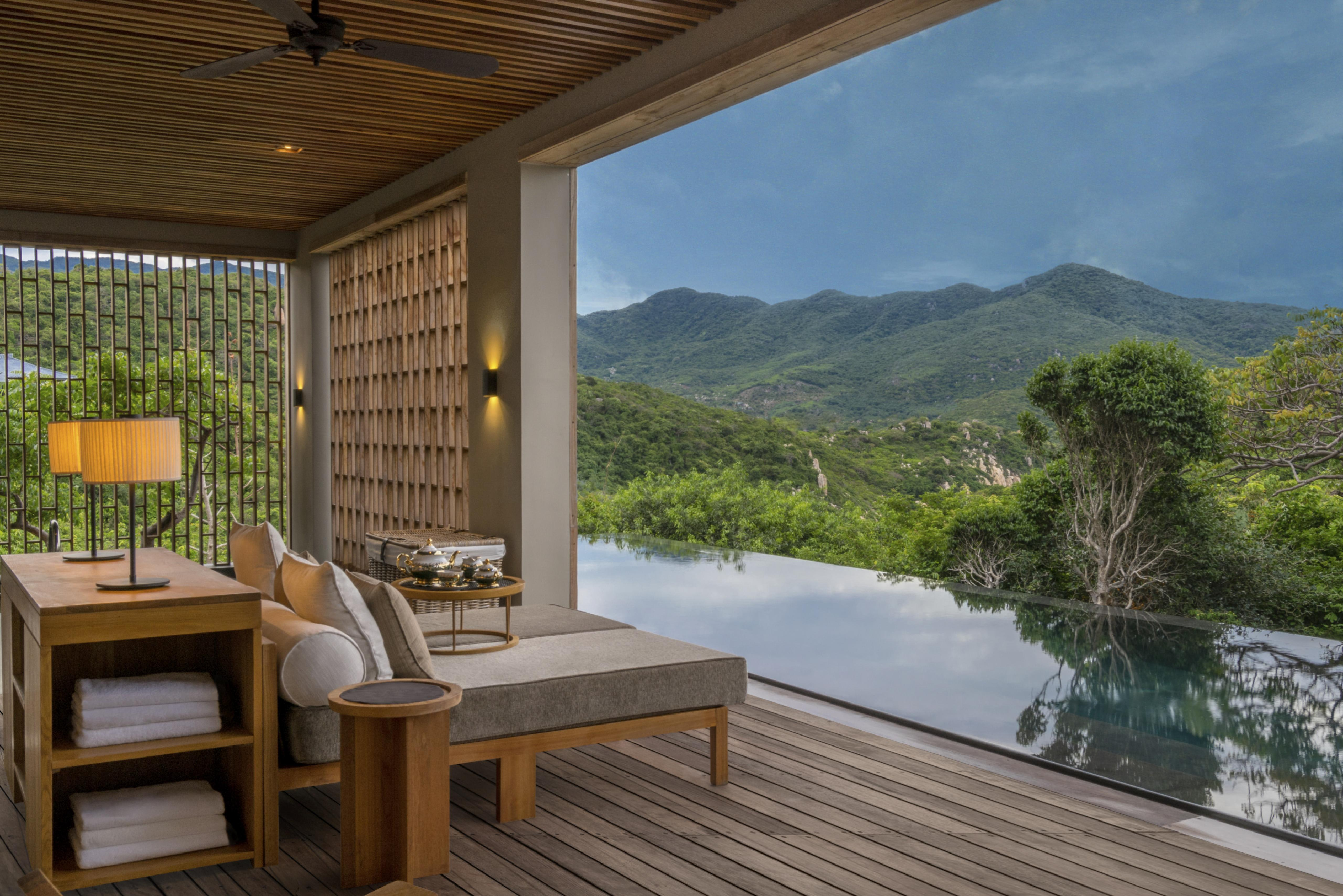 wooden open air seating, overlooking infinity pool and green mountains