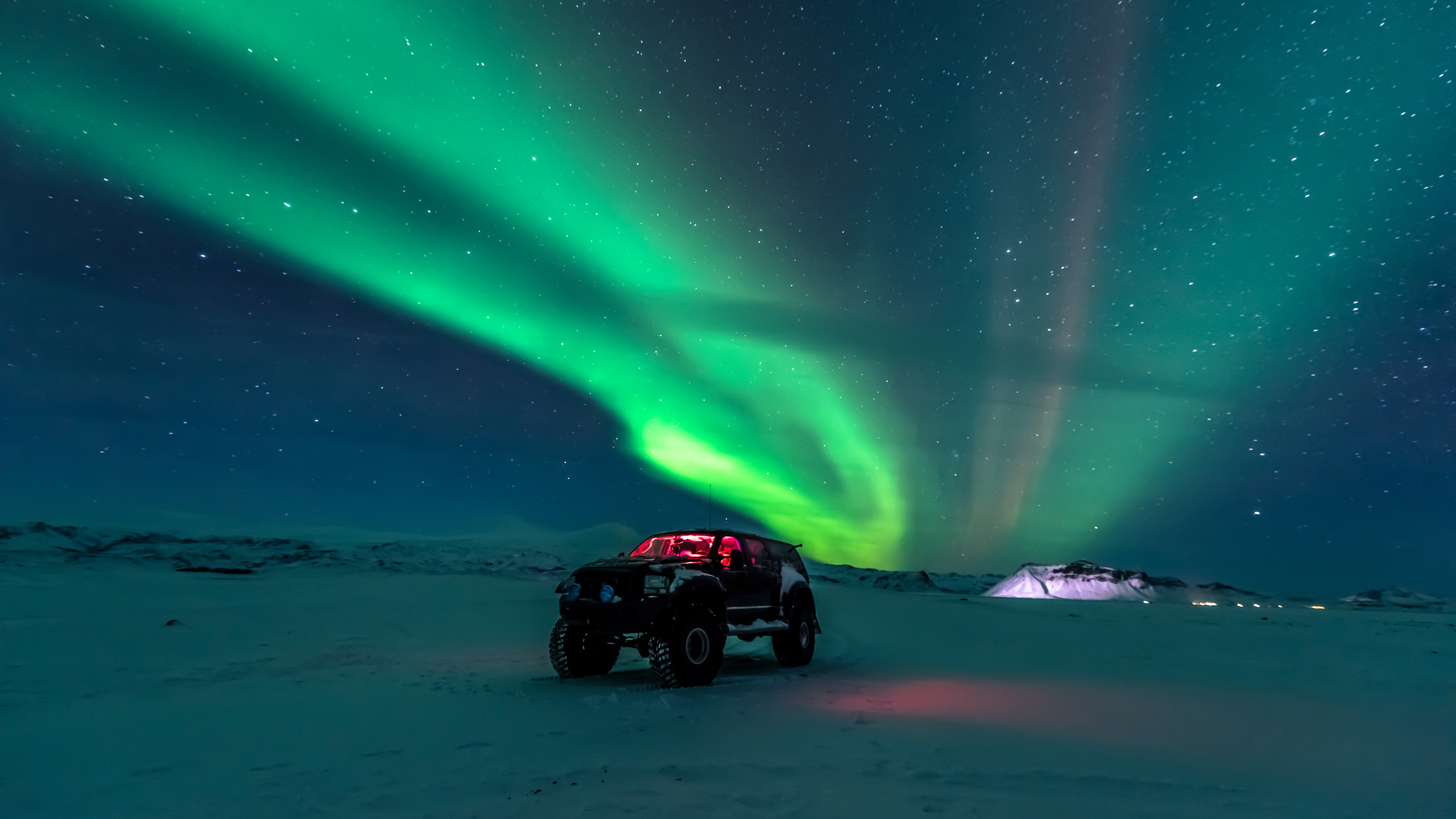 red jeep at night with Aurora Borealis in sky