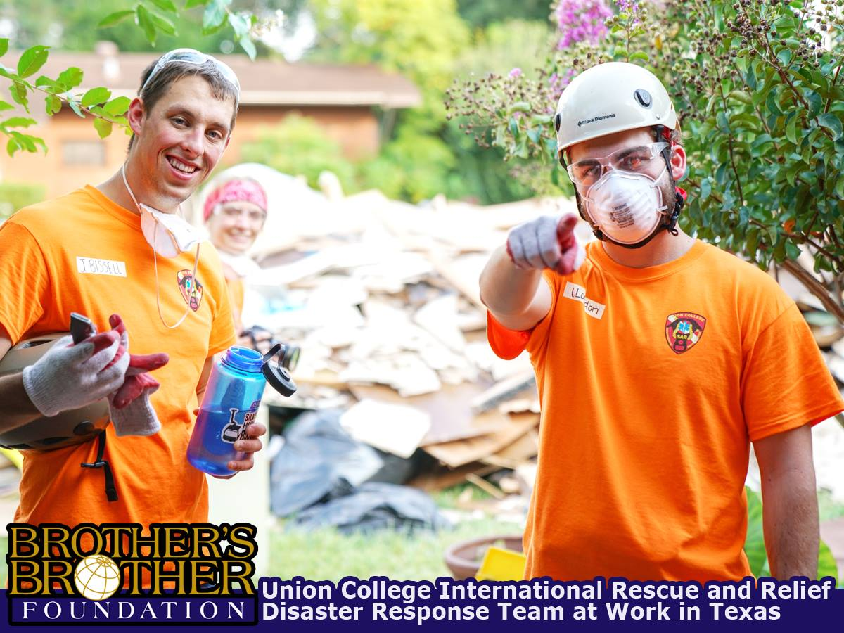 Two men in orange shirts and face masks, pile of construction rubbish behind them