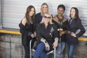 blonde woman with sunglasses sitting, surrounded by four models