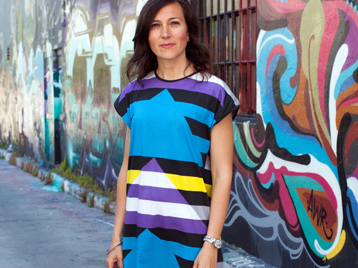 Woman in bright blue and striped dress against graffiti wall