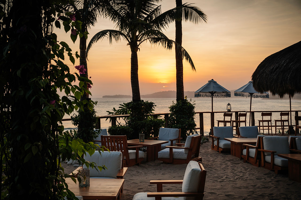 Outdoor dining with sunset and palm trees