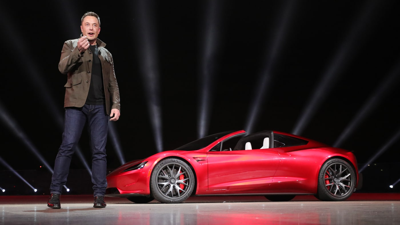 Elon Musk and cherry red Tesla Roadster