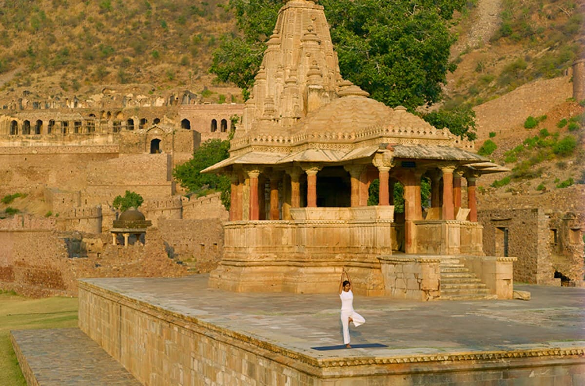 person in white doing yoga with temple backdrop