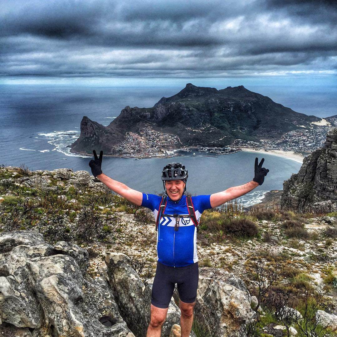 man in blue cycling gear standing above Noordhoek Peak, arms outstretched