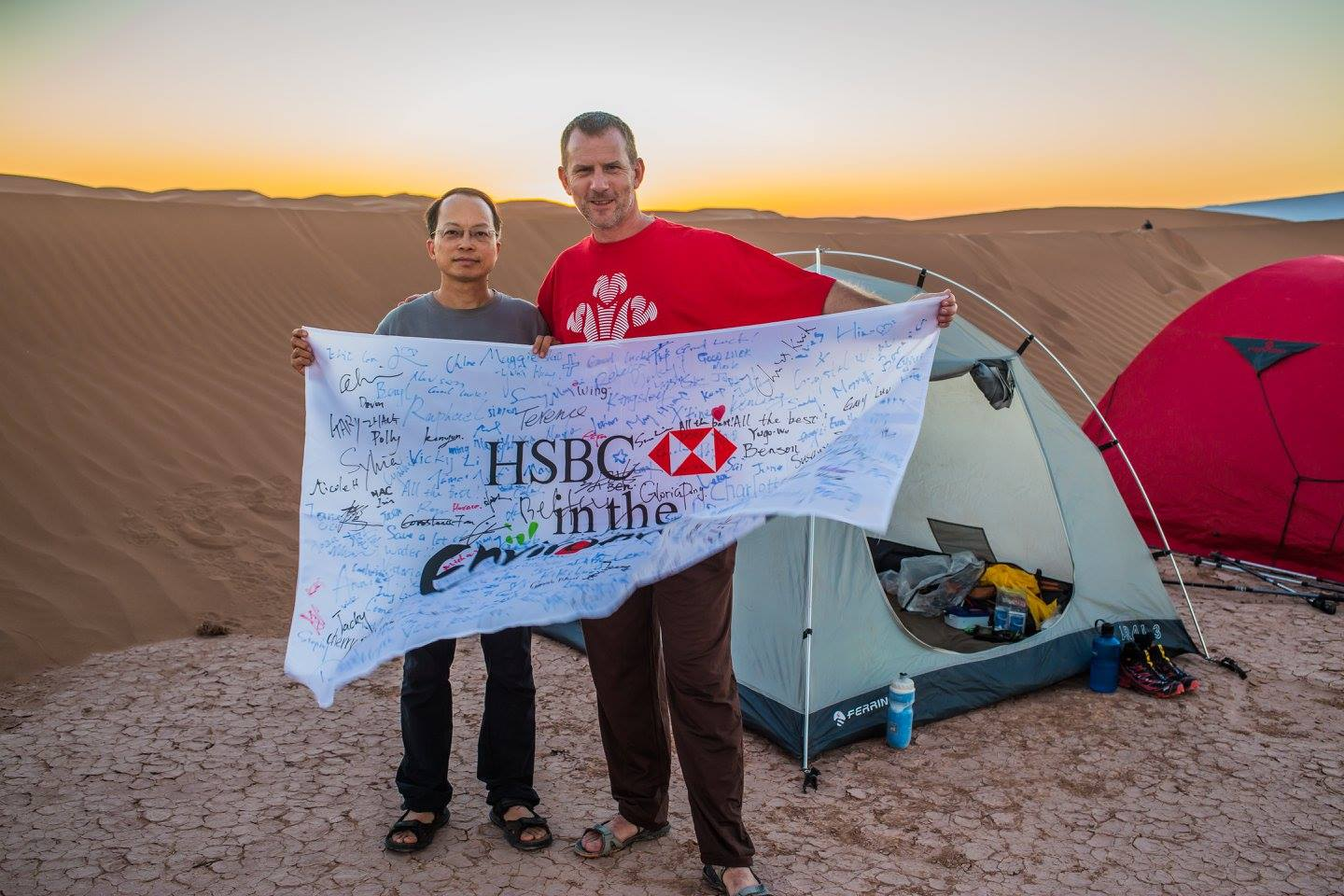 two men holding HSBC white banner with sunset over desert in background