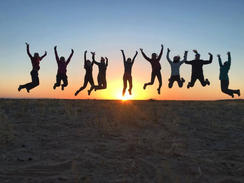 10 people jumping in air with sun setting behind them