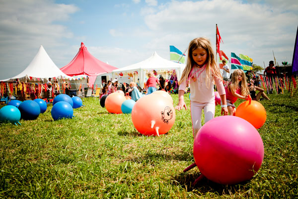 tents, girl on grass with colourful balls