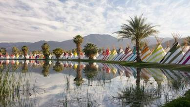 colourful teepees next to a calm lake with palm trees