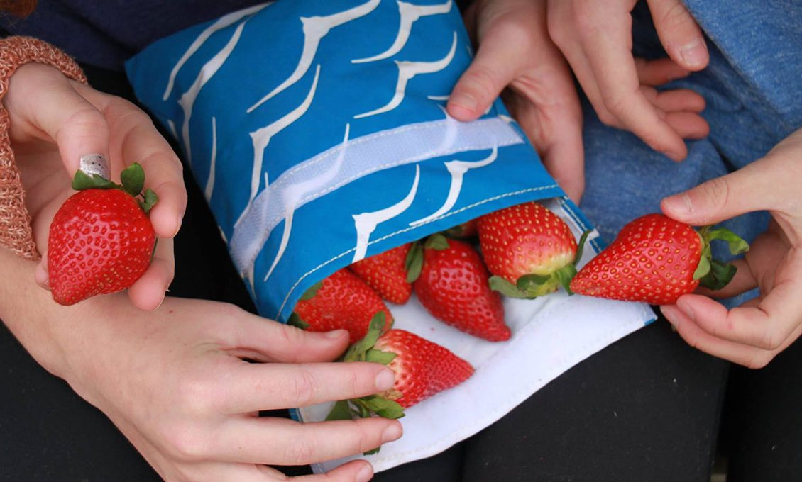 hands taking out bright red strawberries from a blue reusable cloth bag