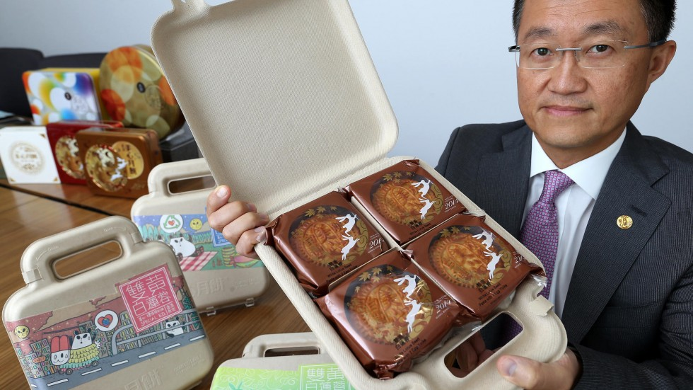 Asian man holding mooncake box open