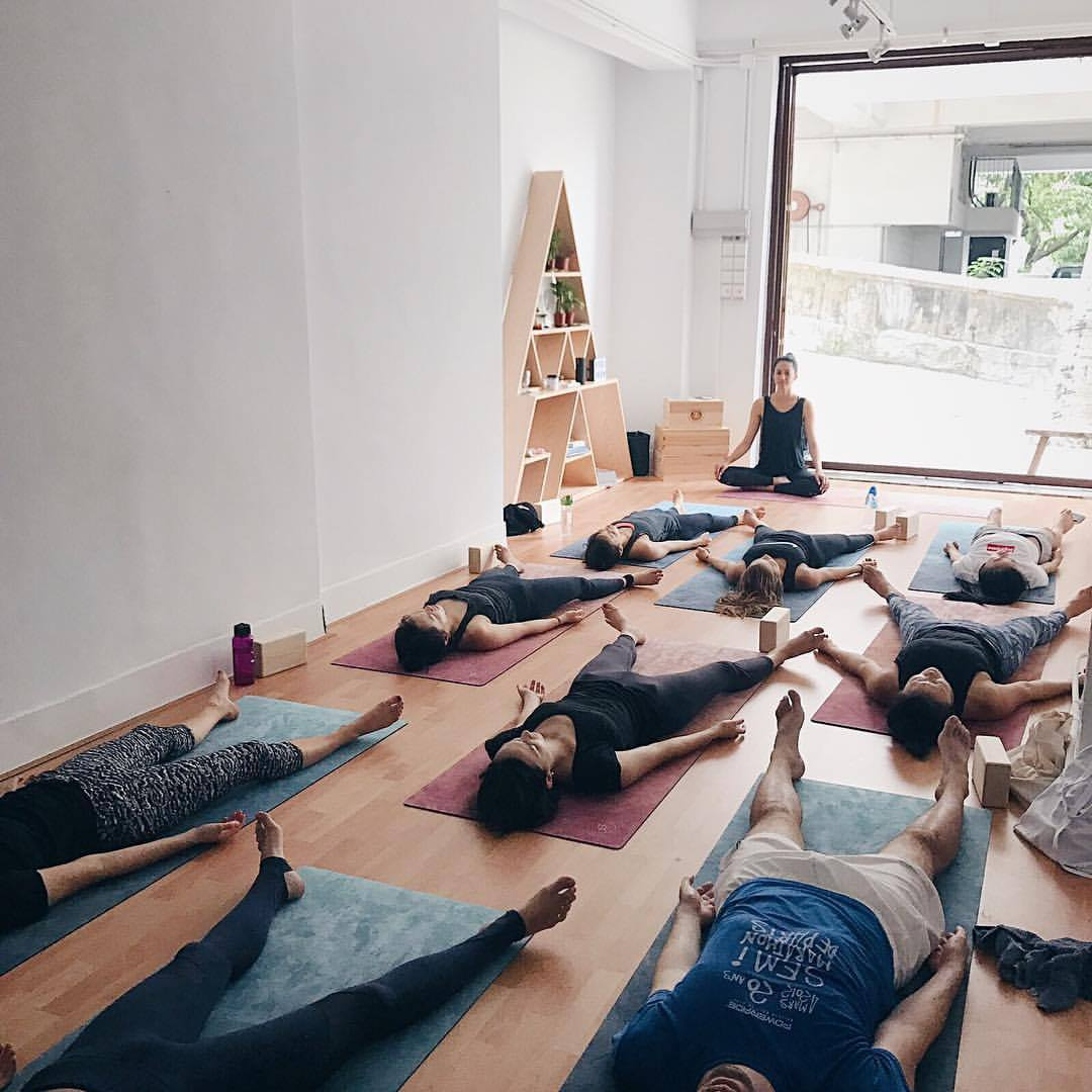 yoga class, students lying on yoga mats with teacher in lotus position
