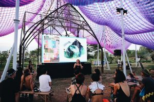 purple tent, audience on benches, presentation