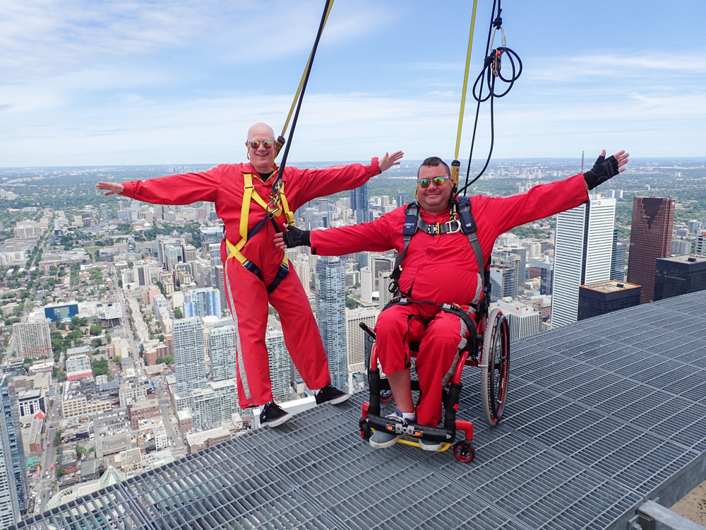 two men in red suits on Edgewalk, CN Tower, one in wheelchair