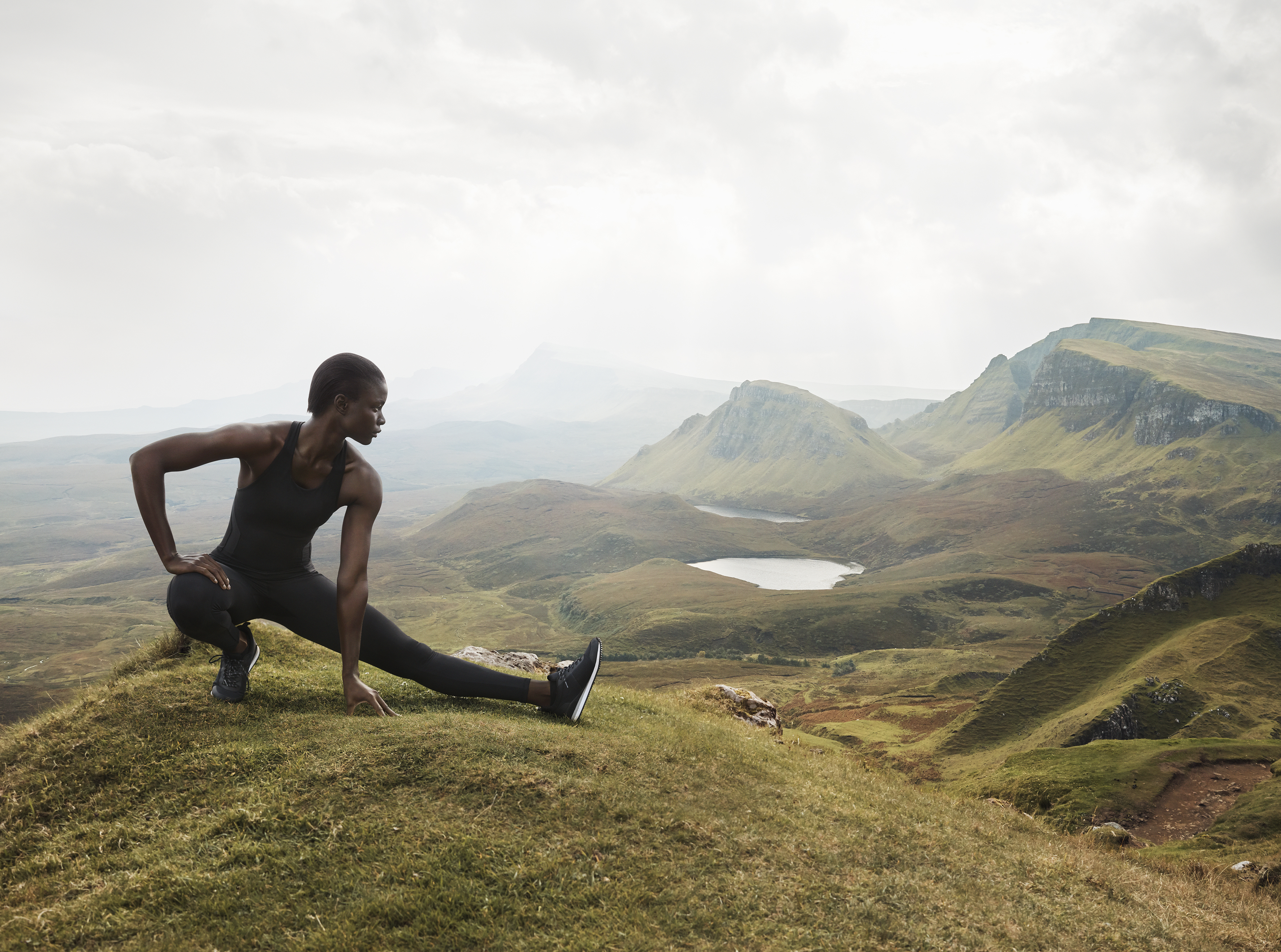Dark-skinned woman stretching on mountain top