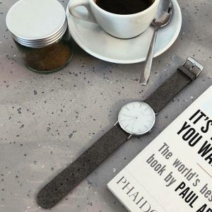taupe watch on table next to coffee cup and book