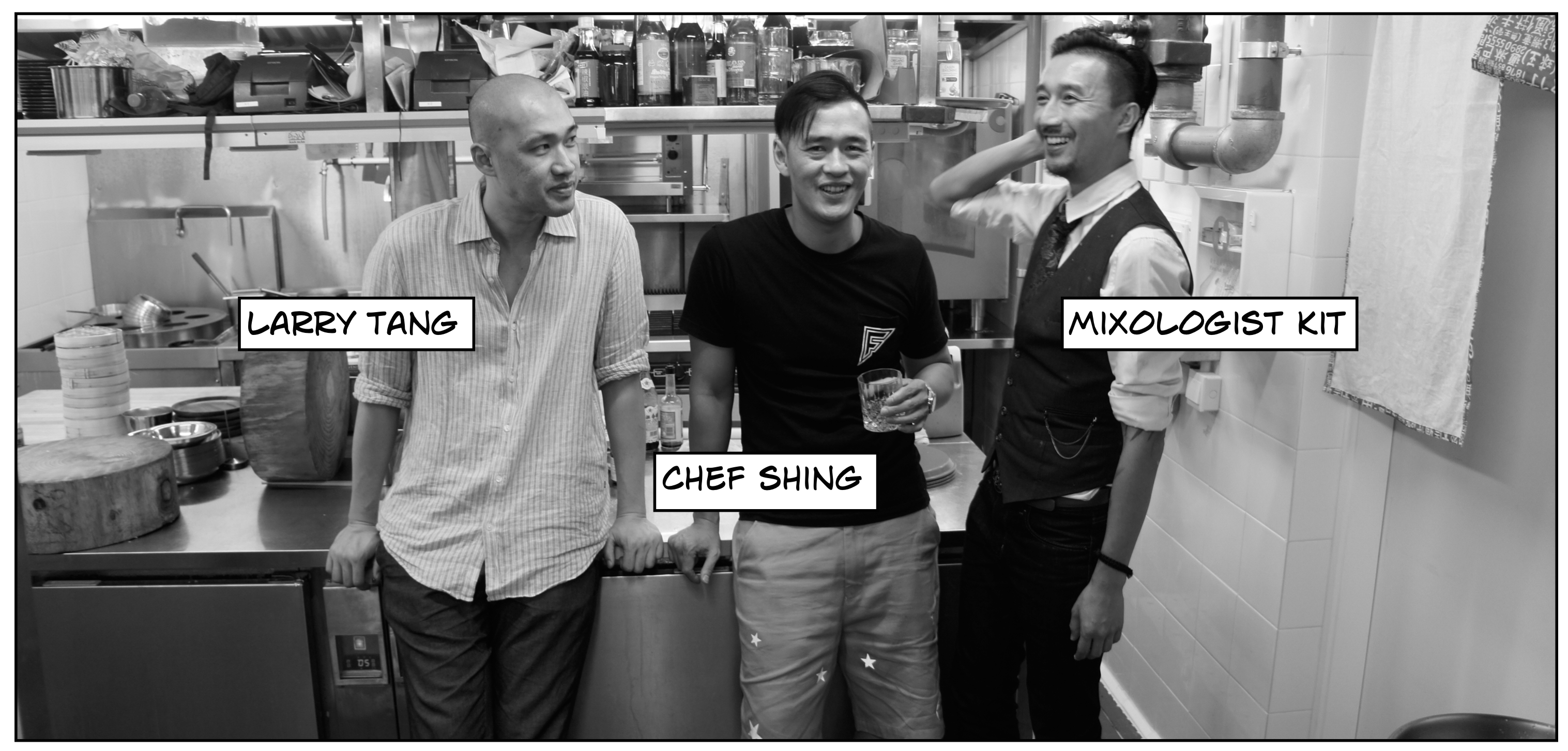 black and white photo of three men standing against a kitchen counter