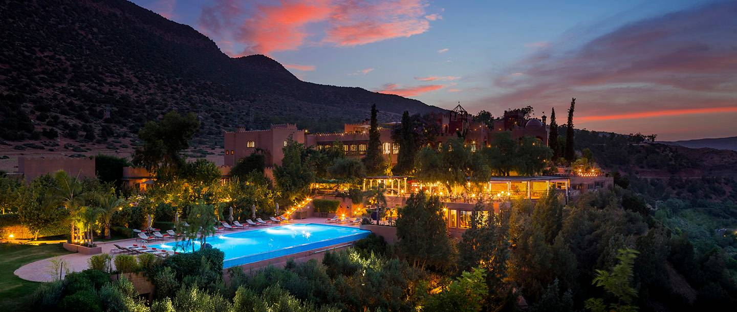 large hotel lit at night, blue pool, dusky sunset