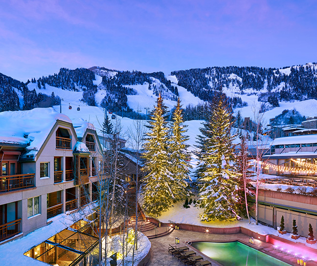 snowy mountains, hotel at dusk, trees