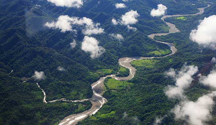brown, muddy river snaking between green mountains