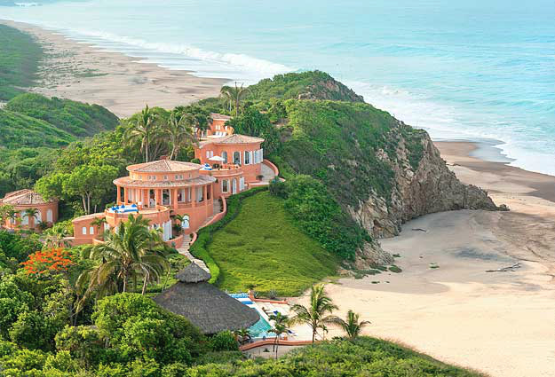 terracotta coloured villas perched on cliff with beaches and pacific ocean below