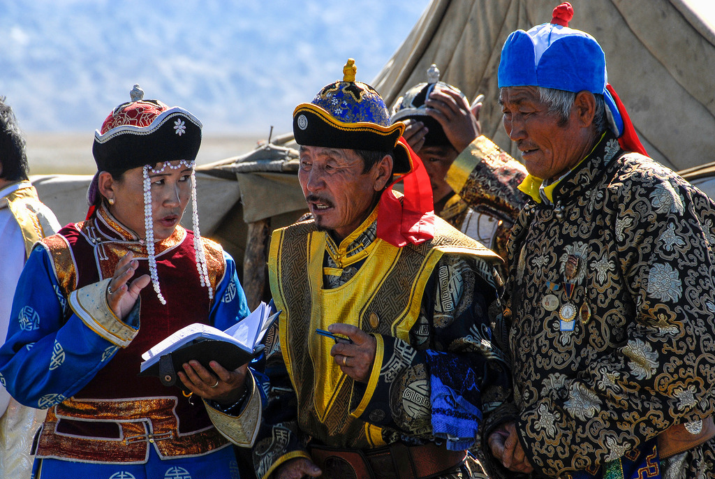 four men dressed in colourful Mongolian outfits and hats