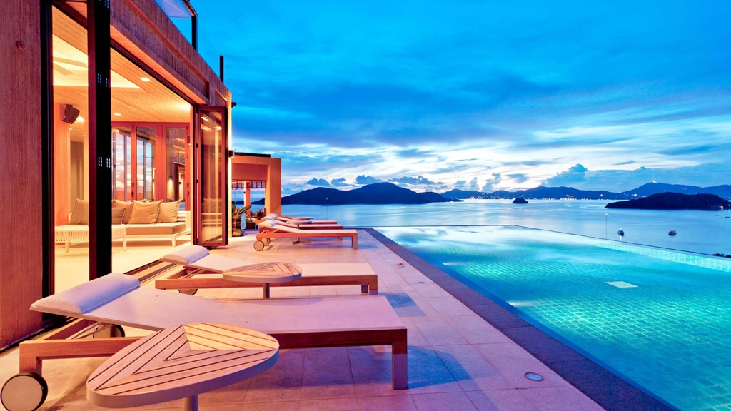pool villa at dusk, overlooking blue infinity pool