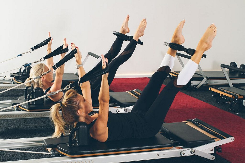 three women on pilates machines, feet and legs in straps