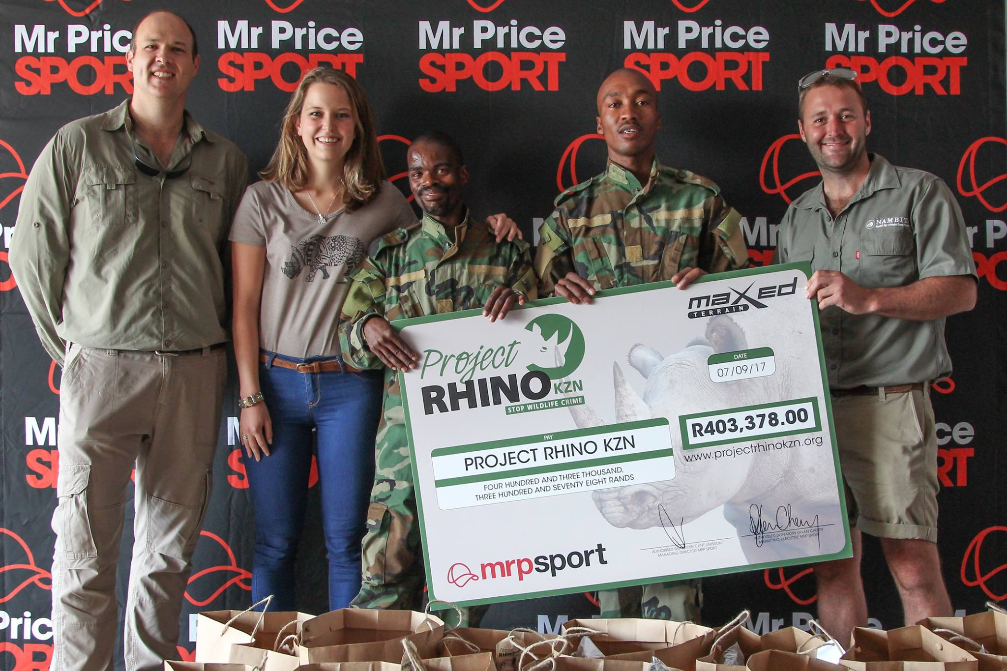 five people holding large Project Rhino donation check