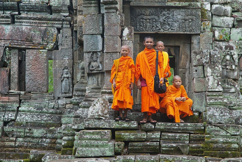 orange-robed young monks standing on temple steps