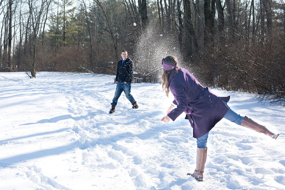 woman in purple coat throwing snowball at man