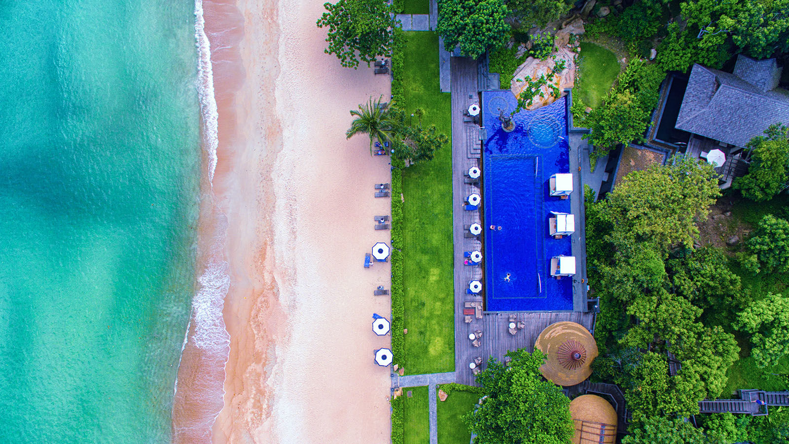 aerial view of beachfront hotel with bright blue infinity pool