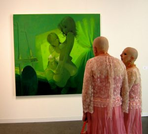 two identical women, looking at green painting