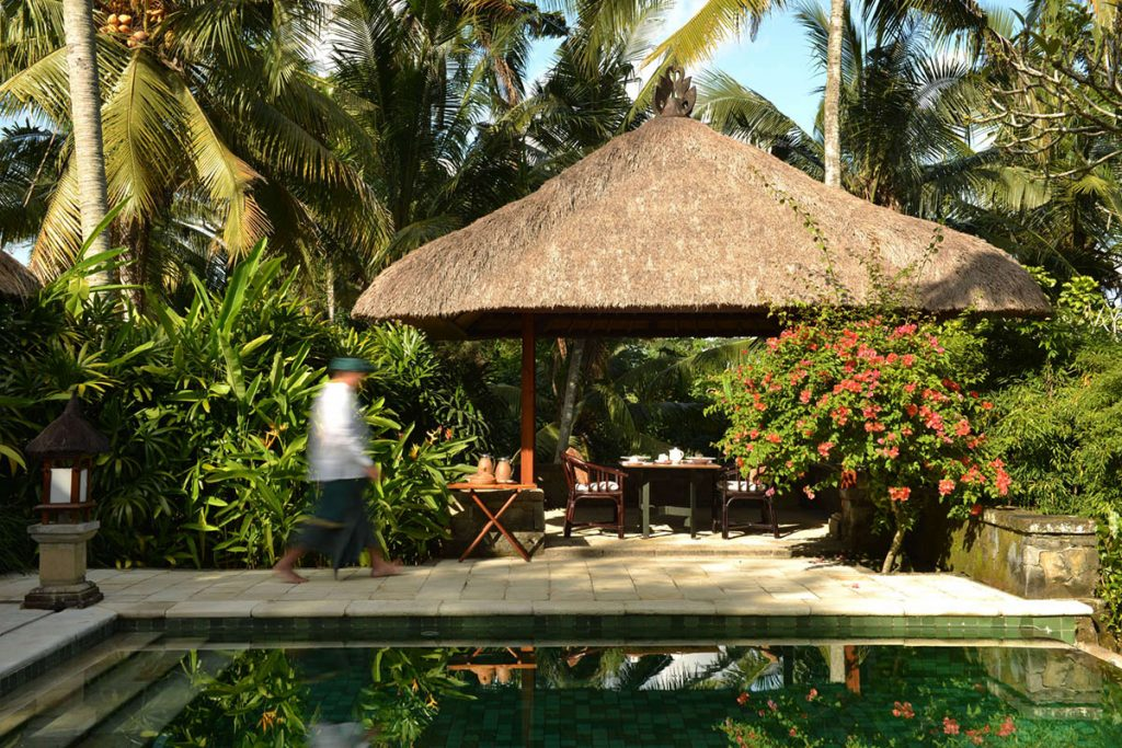 thatched hut, person walking, private pool
