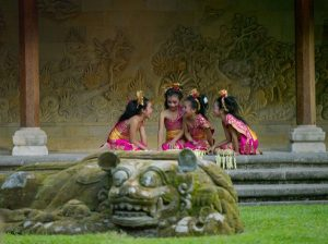 four girls in pink Indonesian costumes, kneeling