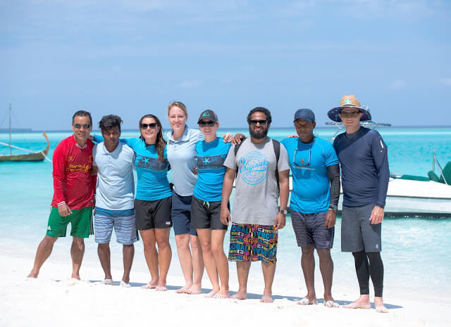 eight people in sunglasses, tropical beach