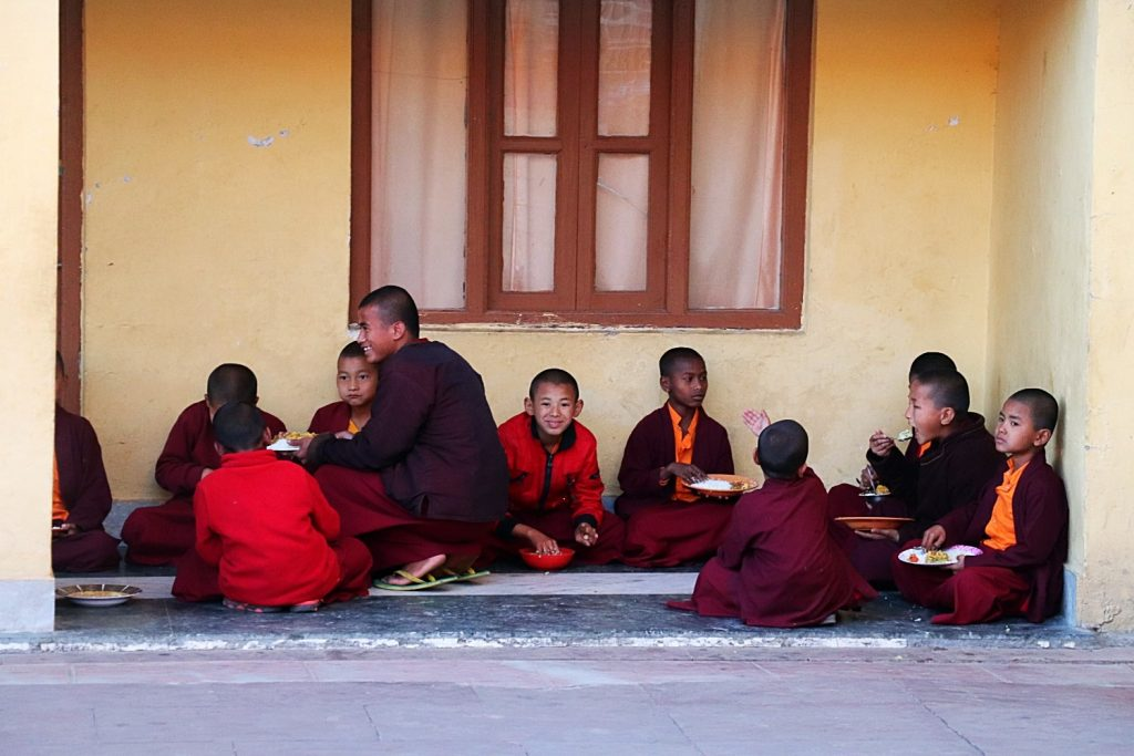 group of young maroon-robed monks sitting outside