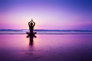 pink sunset, person cross legged in yoga pose