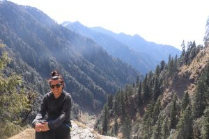 woman sitting in front of mountain landscape in Himalayas