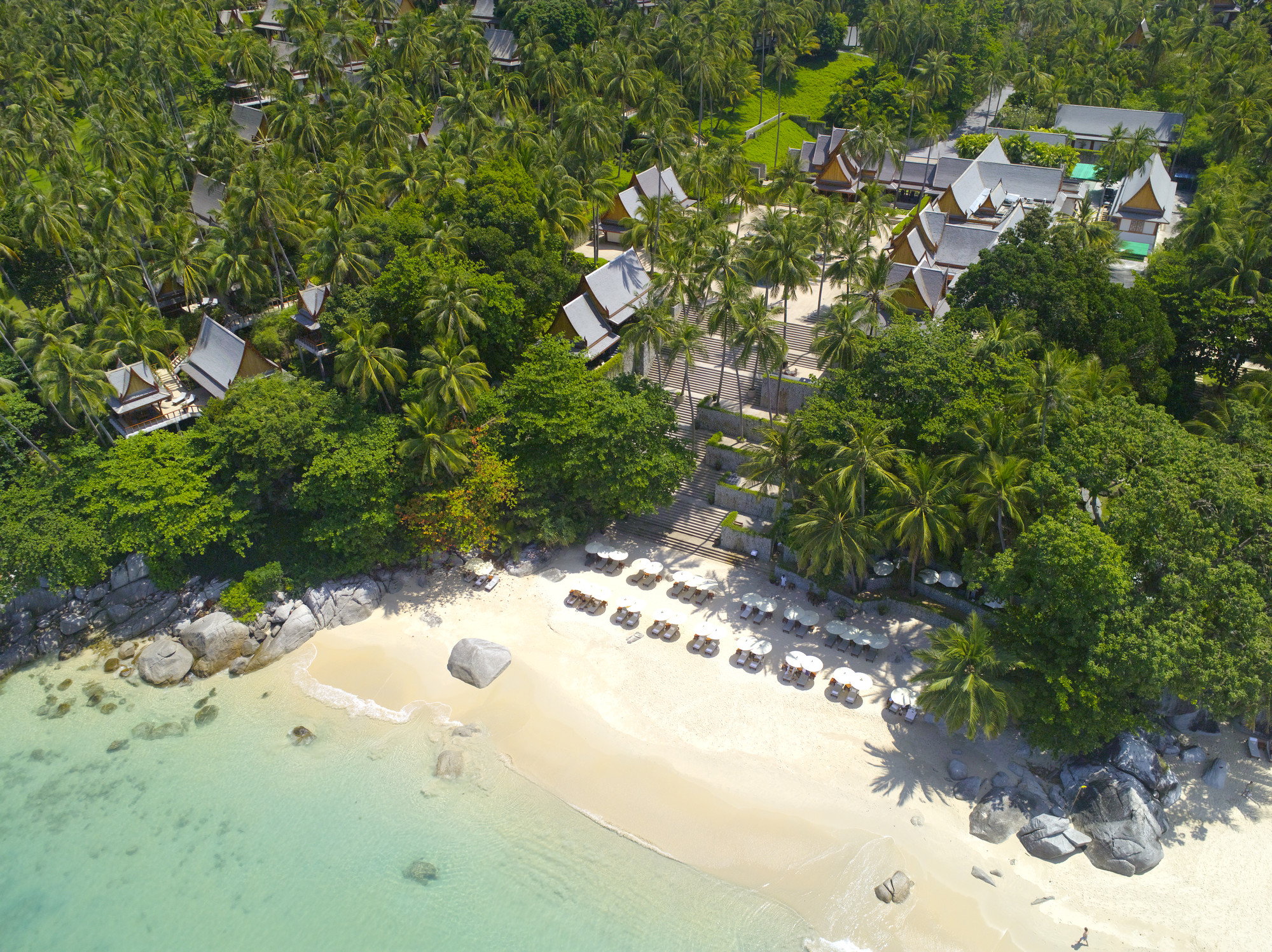 aerial view of white sand beach, turquoise water and beachfront hotel pavilions