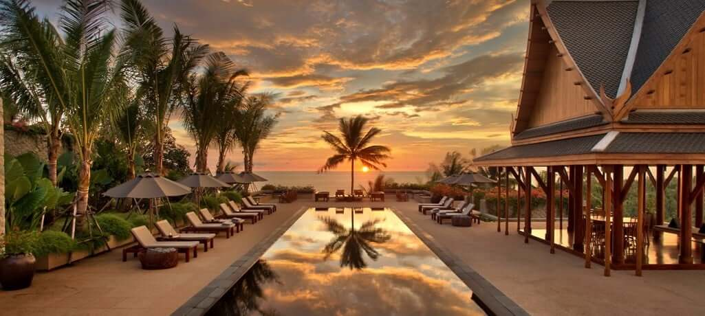 sunset over private villa pool, palm trees