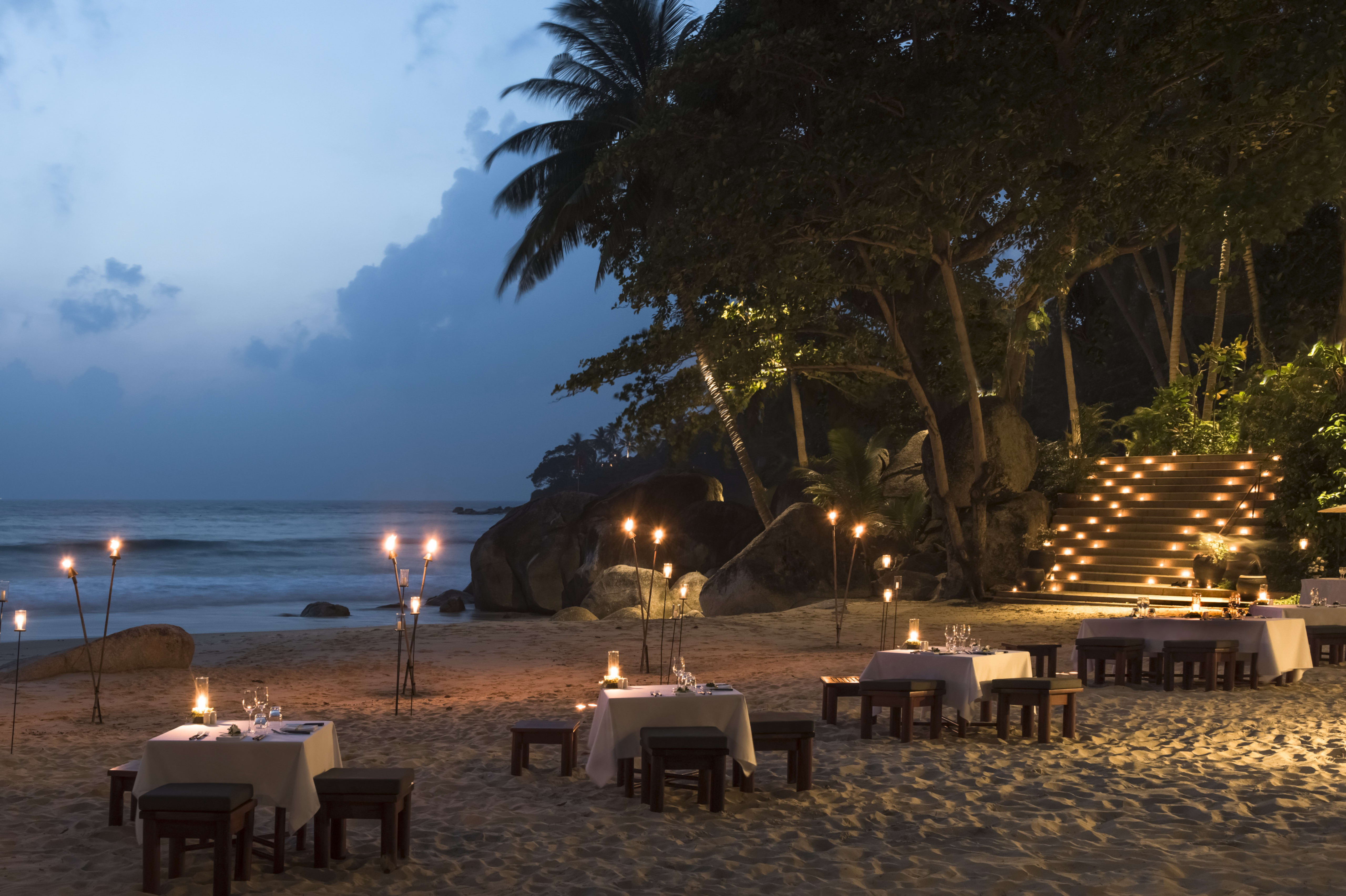 white tablecloth tables on beach, sunset