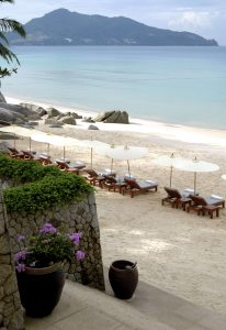 beach loungers and umbrellas on white sand beach